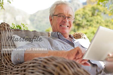 Portrait of smiling man using digital tablet on patio