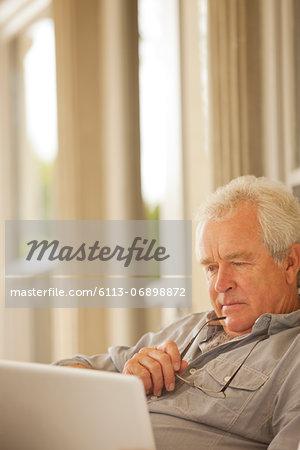 Serious senior man using laptop
