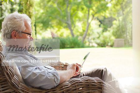 Senior man using digital tablet in wicker armchair on porch