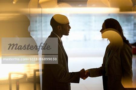Businessman and businesswoman handshaking in lobby