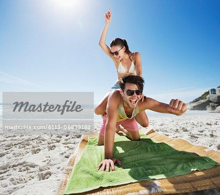 Woman piggybacking enthusiastic man on beach