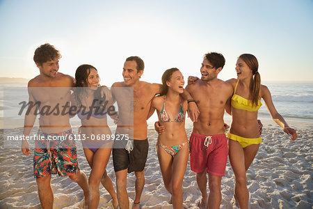 Happy friends in bikinis and swim trunks walking on beach