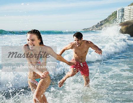 Playful couple splashing in ocean surf