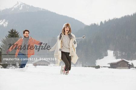 Happy couple running in snowy field