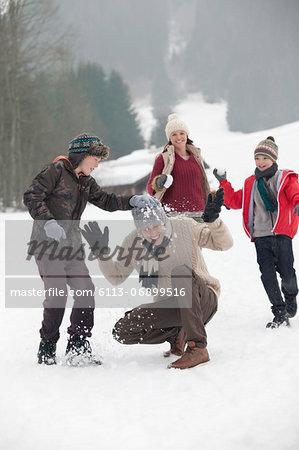 Happy family enjoying snowball fight in field