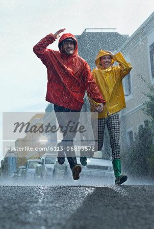 Happy couple in raincoats running down street in rain