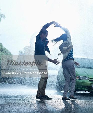 Happy couple dancing in rain