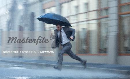 Businessman with umbrella running across rainy street