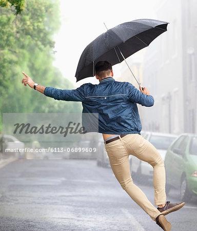 Man dancing with umbrella in rainy street