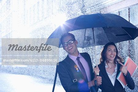 Happy businessman and businesswoman walking under umbrella in rain