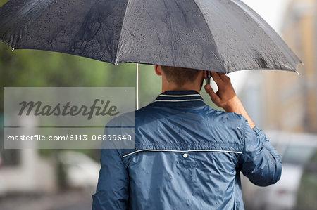 Man talking on cell phone under umbrella in rain