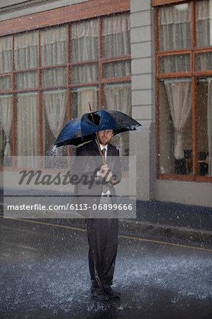 Businessman standing under broken umbrella in rainy street