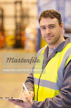 Worker using clipboard in warehouse