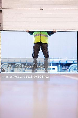 Worker lifting door in warehouse