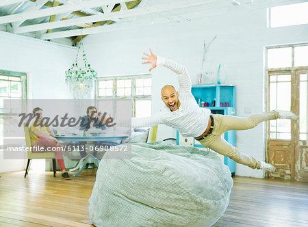 Man jumping into beanbag chair