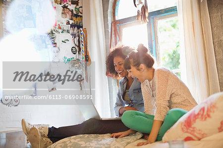 Women using laptop together in bedroom
