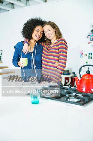 Women hugging in kitchen