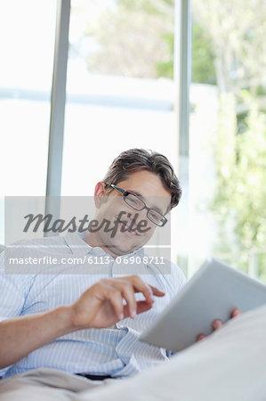 Man using tablet computer on sofa
