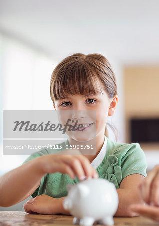 Girl filling piggy bank on counter