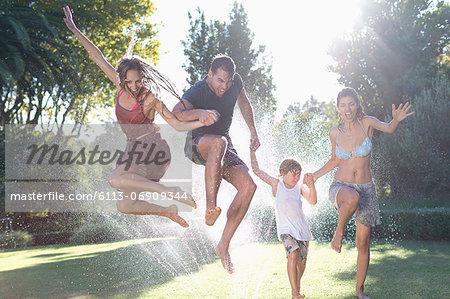 Family jumping in sprinkler
