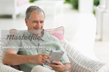 Older man using tablet computer on porch