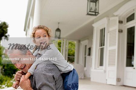 Older man carrying granddaughter piggy back on porch