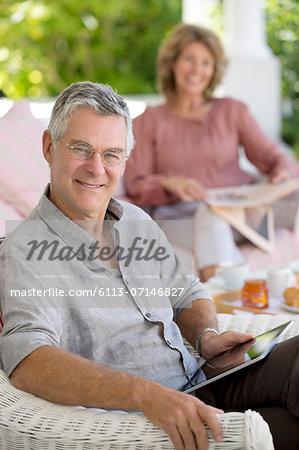 Senior man using digital tablet in armchair on patio
