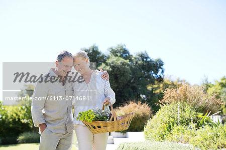 Senior couple walking with basket outdoors