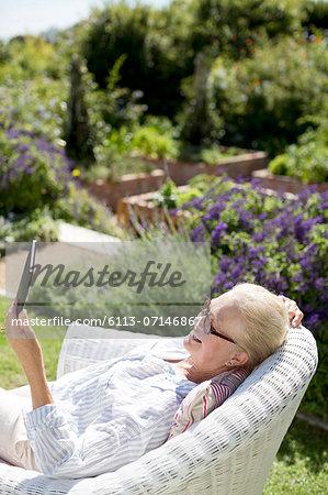 Senior woman using digital tablet in garden