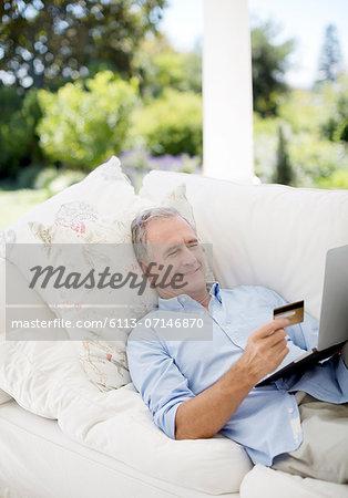 Senior man shopping online on patio sofa