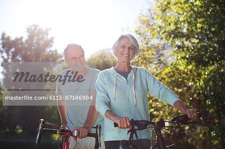 Senior couple walking bicycles in park