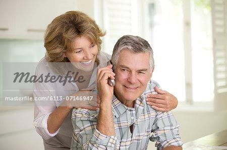 Senior couple talking on telephone
