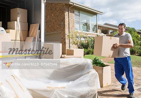Man carrying cardboard box to moving van in driveway