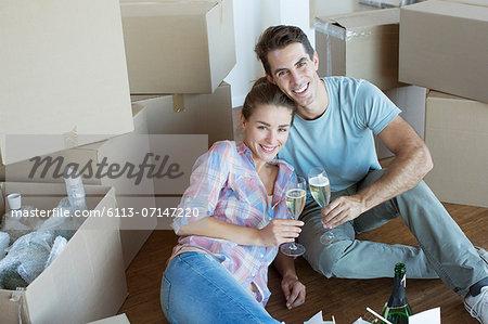 Portrait of couple enjoying champagne among cardboard boxes