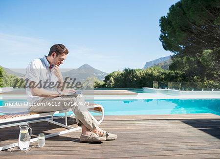 Man using laptop at poolside