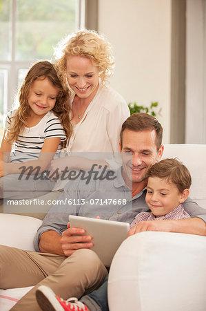 Family using digital tablet on sofa