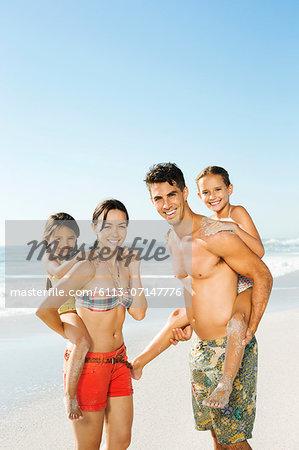 Parents carrying daughters piggyback on beach
