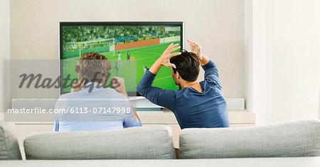 Men watching soccer game on sofa