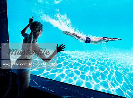 Woman watching boyfriend underwater in swimming pool