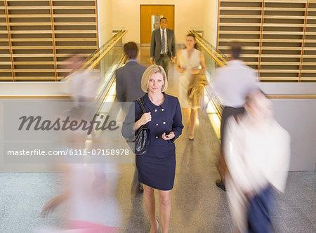 Businesswoman walking in busy office corridor