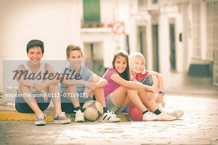 Children with soccer balls sitting on city street