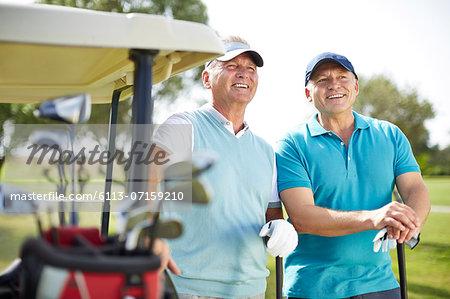 Senior man standing next to golf cart