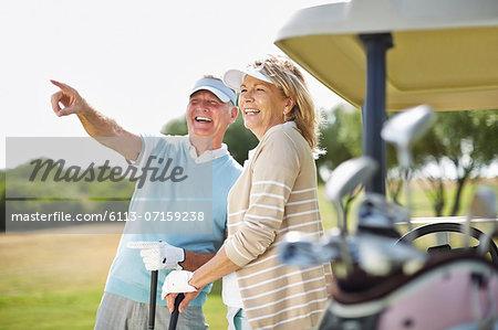 Senior couple standing next to golf cart