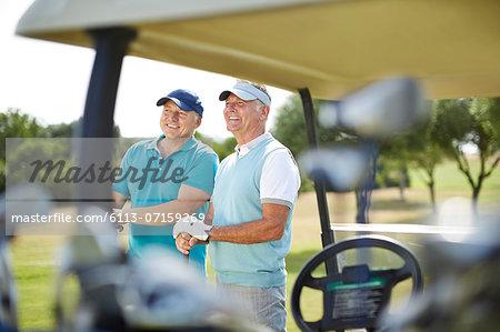Senior men standing next to golf cart