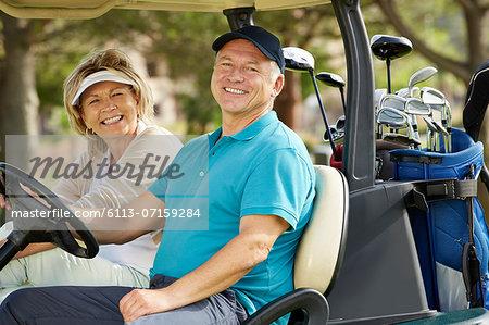 Senior couple smiling in golf cart