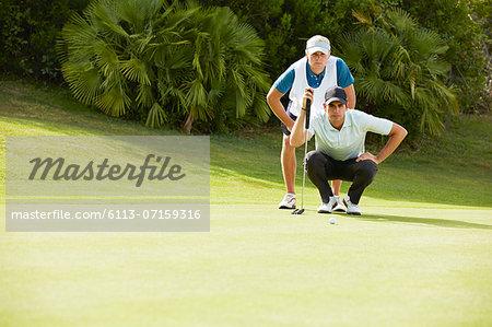Caddy and golfer preparing to putt