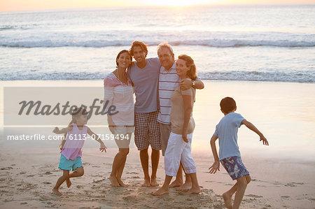 Multi-generation family hugging on beach