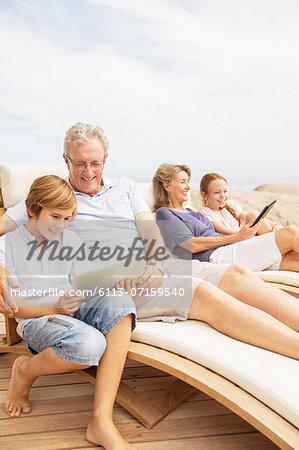 Grandparents and grandchildren using digital tablets at poolside