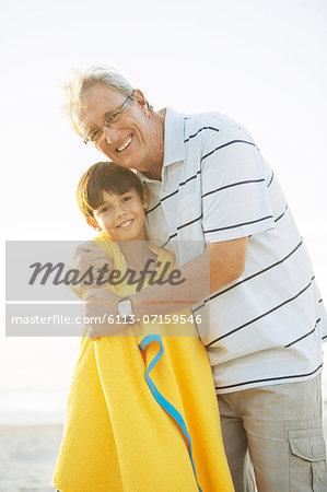 Grandfather hugging grandson on beach