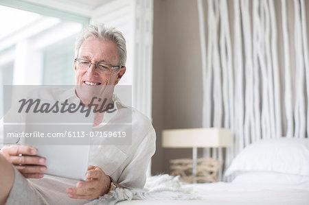 Older man using digital tablet on bed